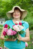 Happy mature woman in garden — Stock Photo