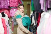женщина с ребенком в ringsling выбирает одежду — Стоковое фото