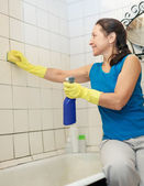 Woman cleans tile with sponge in bathroom — Stock Photo