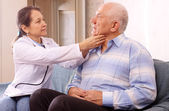 Mature doctor examining senior patient — Stock Photo