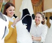 Shop assistent hjälper till att flicka väljer vit brud outfit — Stockfoto
