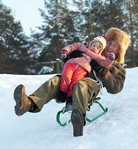 Man with child sliding on sleds downhil — Stock Photo
