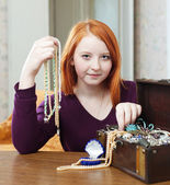Teen girl chooses bead in treasure chest — Stock Photo