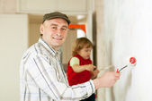 Man with child paints wall — Stock Photo