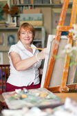 Woman artist paints on canvas — Stock Photo