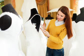 Woman chooses wedding outfit at boutique — Stock Photo