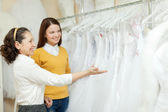 Shop assistant helps bride in choosing dress — Stock Photo