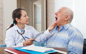 Volwassen arts ziet er de mond van de patiënt — Stockfoto