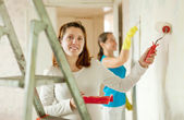 Women paints wall — Stock Photo
