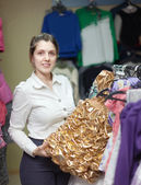 Woman chooses golden dress for daughter — Stok fotoğraf