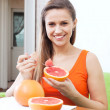 Woman eating grapefruit at home — Stock Photo