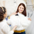 Women chooses bridal outfit at wedding store — Stock Photo #23480305
