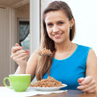 Smiling girl eats buckwheat — Stock Photo