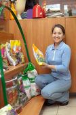 Mujer elige fertilizantes en tienda de jardín — Foto de Stock