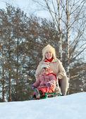 Two-year child sliding downhill on sledge — Stock Photo