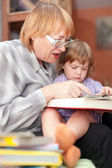 Grandmother and child reads book — Stock fotografie