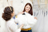 Women chooses bridal outfit at wedding store — Photo