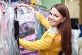 Kobieta kupujący wybiera suknie wieczorowe — Zdjęcie stockowe