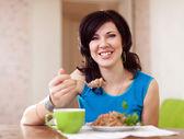 Woman eating buckwheat — Stock Photo