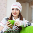 Girl warms with cup of tea at house - Stock Photo