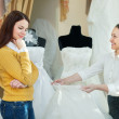 Saleswoman helps girl chooses white bridal gown - Stok fotoğraf