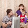 Family at home near oil heater — Stock Photo