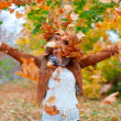 Happy woman throws autumn leaves — Stock Photo