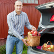 Guy puts apples in the trunk of car - Stock Photo