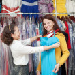 woman chooses evening dress at clothing shop  — Stock Photo
