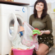 Woman putting clothes in to washing machine -  