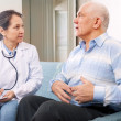 Mature man tells the doctor the symptoms - Stock Photo