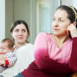 Adult daughter with baby asks for forgiveness from mother — Stock Photo #24183589
