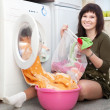 Housewife putting clothes into washing machine - Stockfoto