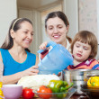 Stock Photo: Women with child together cooking veggie lunch