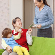 Stock Photo: Mother pays nanny for her child