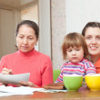 Grandmother mother fills in utility payments bills — Stock Photo #24183963