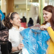 Stock Photo: Buyers chooses evening dress in store