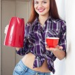 Happy housewife with red kettle and cup - Stock Photo
