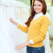 Woman  choosing white dress at shop - Stockfoto