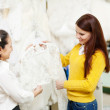 Consultant helps bride chooses bridal clothes at shop - Stockfoto
