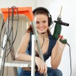 happy sexy girl  in headphones  with drill  — Stock Photo