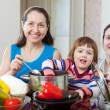 Stock Photo: Mature womand adult daughter with girl cook lunch