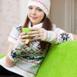 Woman in hat warms with cup of tea - Stock Photo