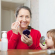 Grandmother with gitl puts facepowder - Stockfoto