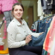 woman chooses blue jeans at shop — Stock Photo