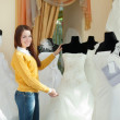 bride chooses wedding outfit in bridal boutique — Stock Photo