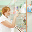 Woman near counter in drugstore - Stock Photo