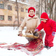 Mother with child cleans rug with snow — Stock Photo