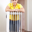 Stock Photo: Smiling womnear warm radiator
