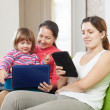 Two women and child looks devices — Stock Photo
